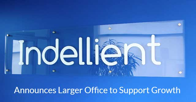 Photo of the Indellient sign against a light blue wall, taken in the Indellient Toronto office foyer
