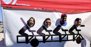 Team members pose on the bike before the bike.
