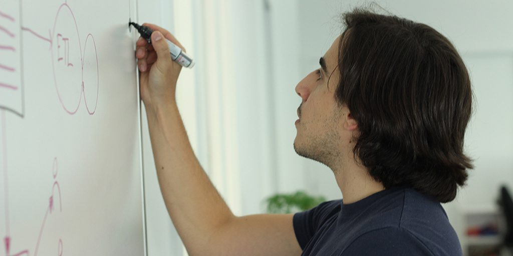 Photo of a man with shoulder length black hair, wearing a dark navy shirt, writing on a whiteboard