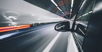 Image of the outside of a car which driving in a tunnel, with the driver side rear view mirror visible and a time lapse streak of lights on the left side indicating other moving cars