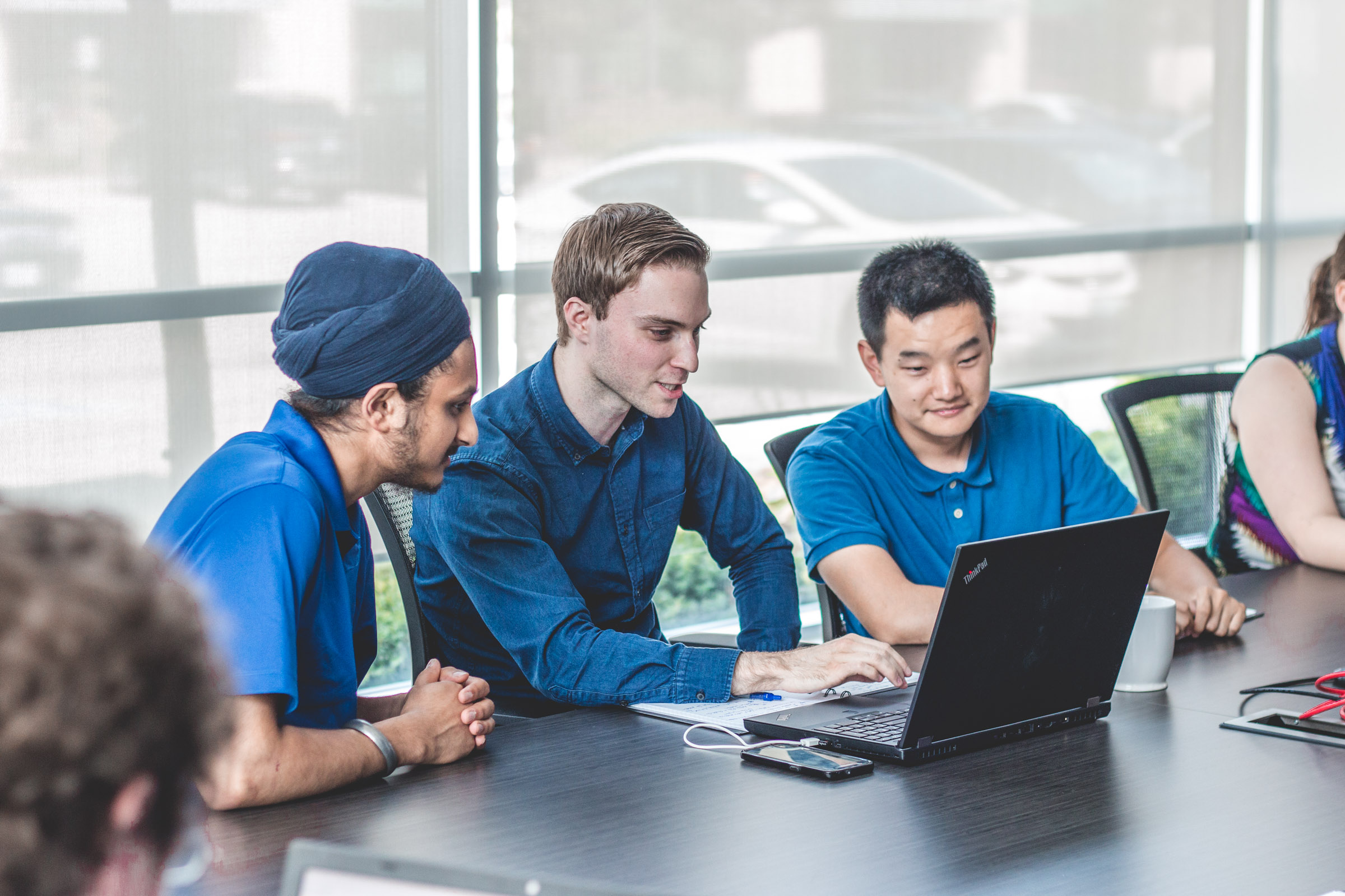 Image of three men sitting beside each other, all wearing blue collard shirts of varying tones, looking at a sinhgle laptop screen with the central person using the laptop and talking/explaining something to the other two