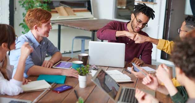work team celebrating around their laptops