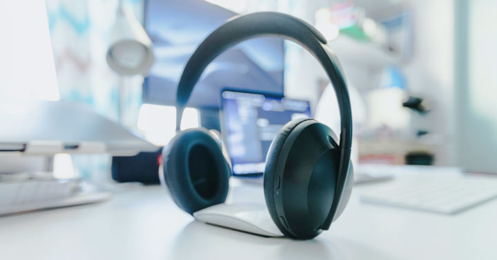 image of headphones on desk with computer in bg