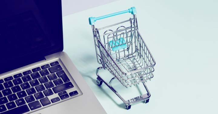 A shopping cart next to a laptop